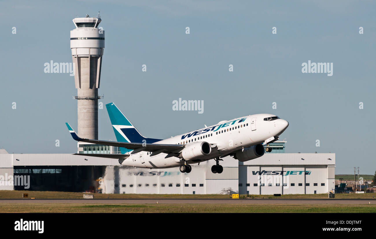 A Westjet Boeing 737-700 jetliner takes off from Calgary International Airport - Stock Image