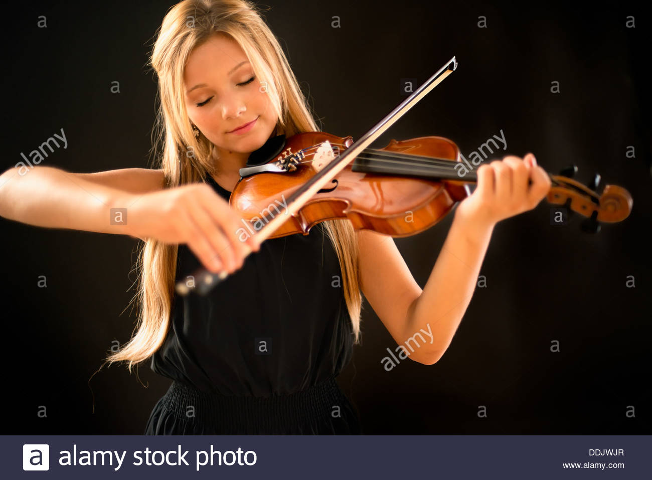 teen girl playing a violin on a black background with her