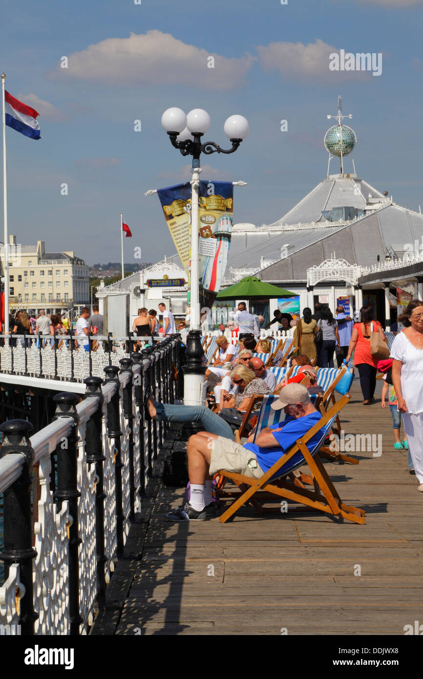 Holidaymakers snoozing in the sun on Brighton Pier, East Sussex, England, UK - Stock Image