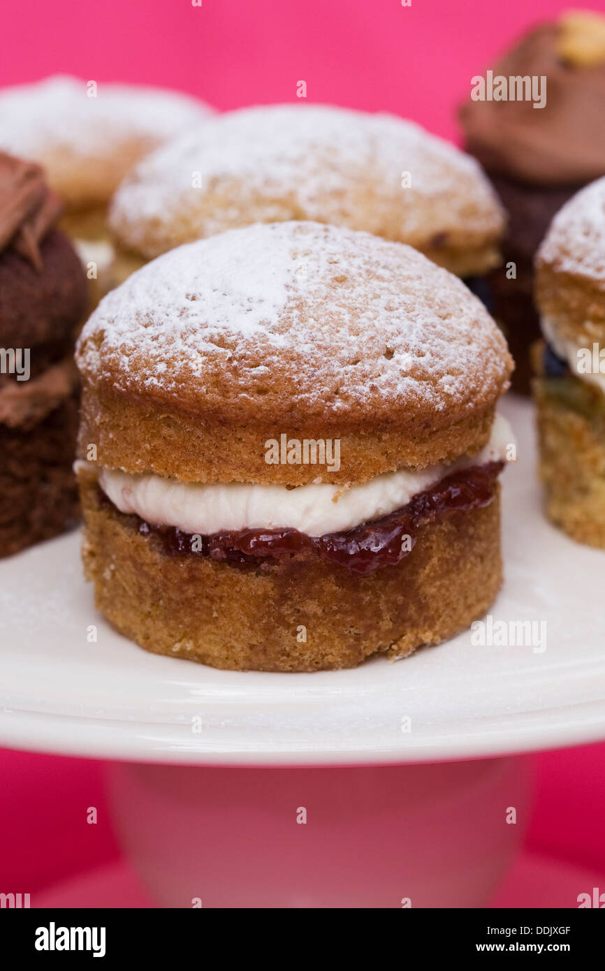 A selection of homemade mini Victoria sandwich cakes on a pink background. - Stock Image