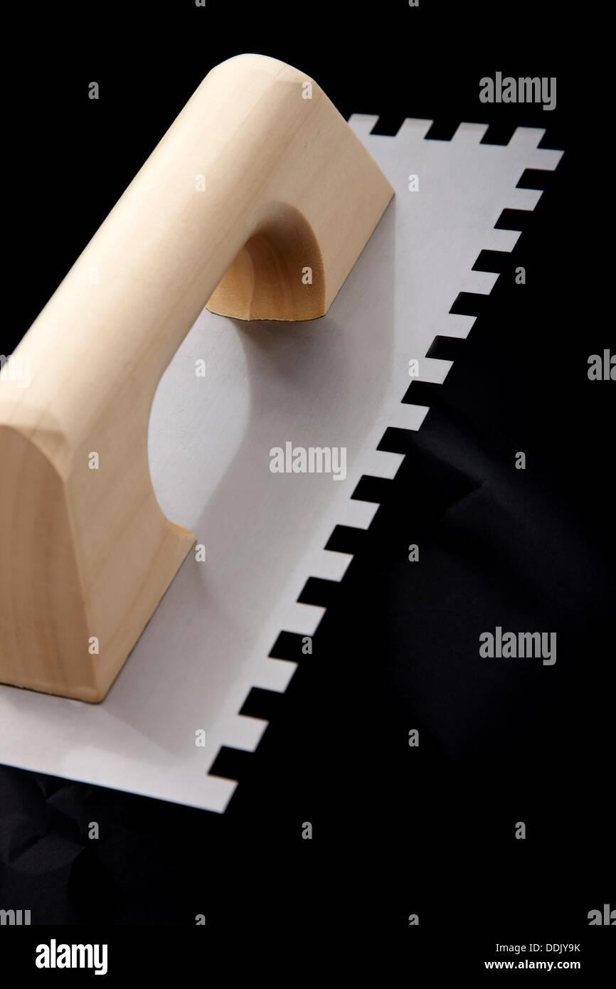 Serrated plastering trowel - Stock Image
