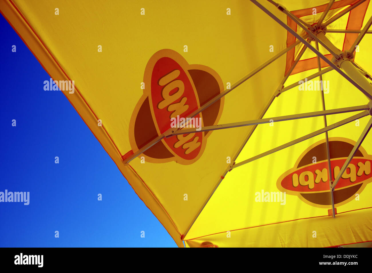 Yellow sunshade against a blue sky - Stock Image