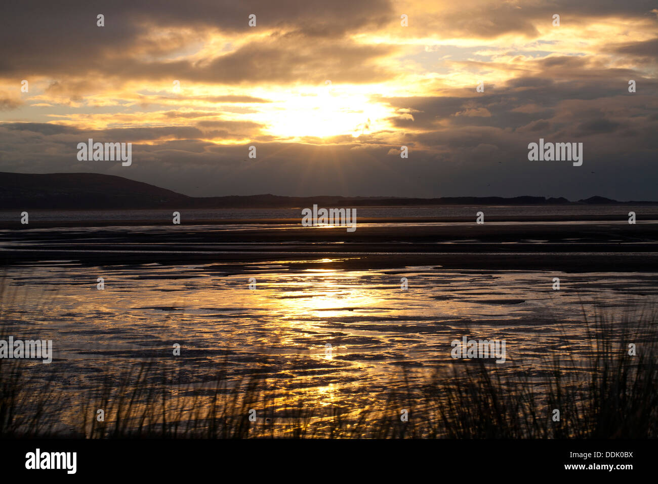 View across the estuary of the River Loughor, from Llanelli to the Gower peninsular at sunset. Carmarthenshire. Stock Photo