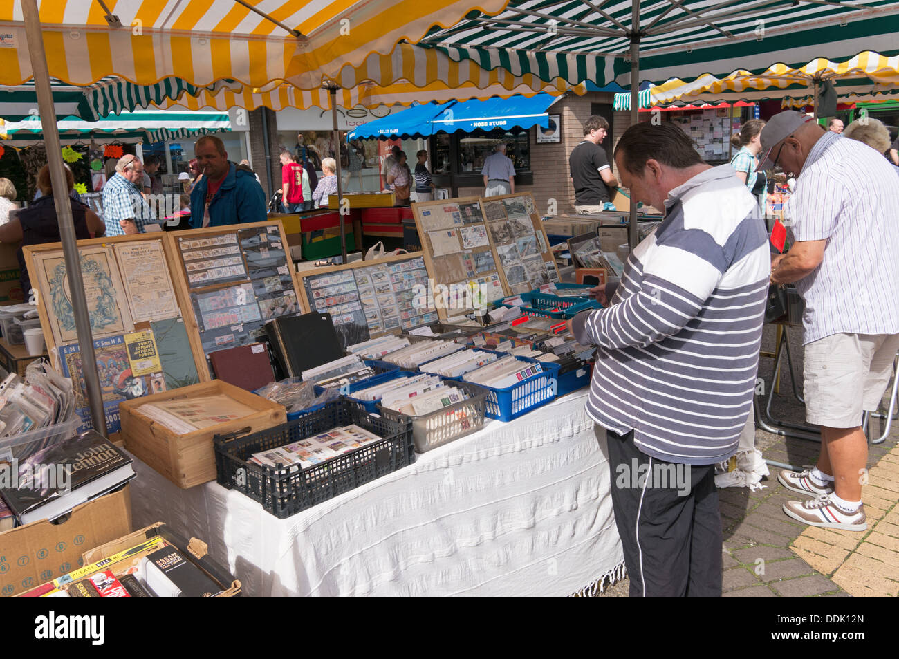 Man browsing through postage stamp collection on market stall in Newton Abbot, England, UK - Stock Image