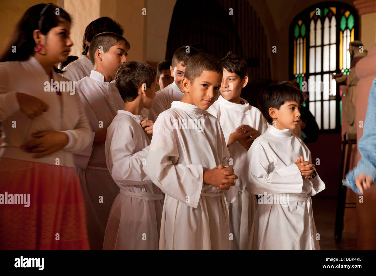 young Altar server during the Mass at the church Iglesia de Nuestra Senora de La Merced in Camagüey, Cuba, Caribbean, - Stock Image