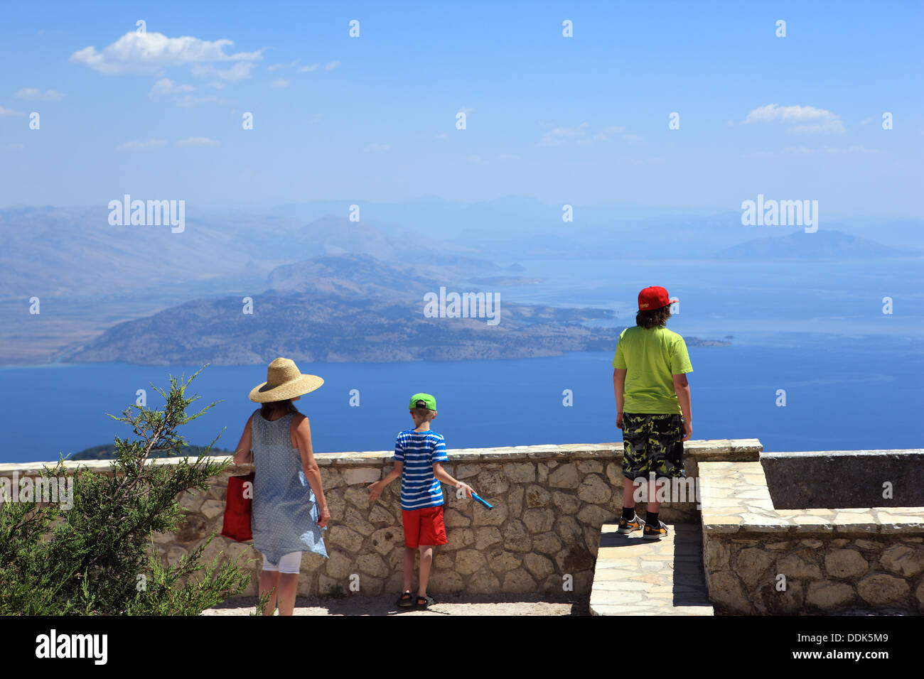 Visitors looking towards Albania from the church on the summit of Mount Pantokrator which is the highest peak on Corfu at 906m - Stock Image