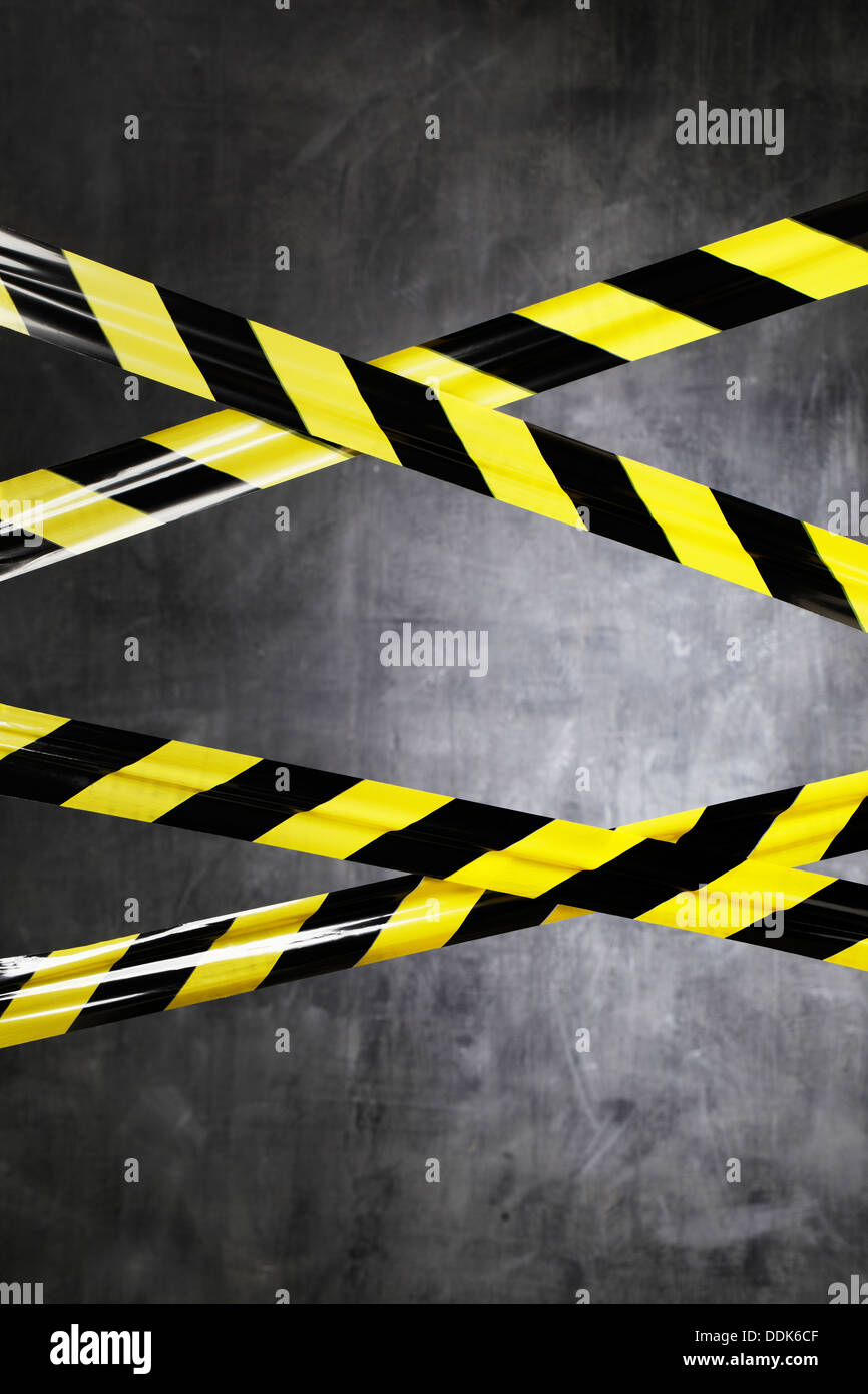 Black and yellow plastic barrier tape blocking the way. - Stock Image