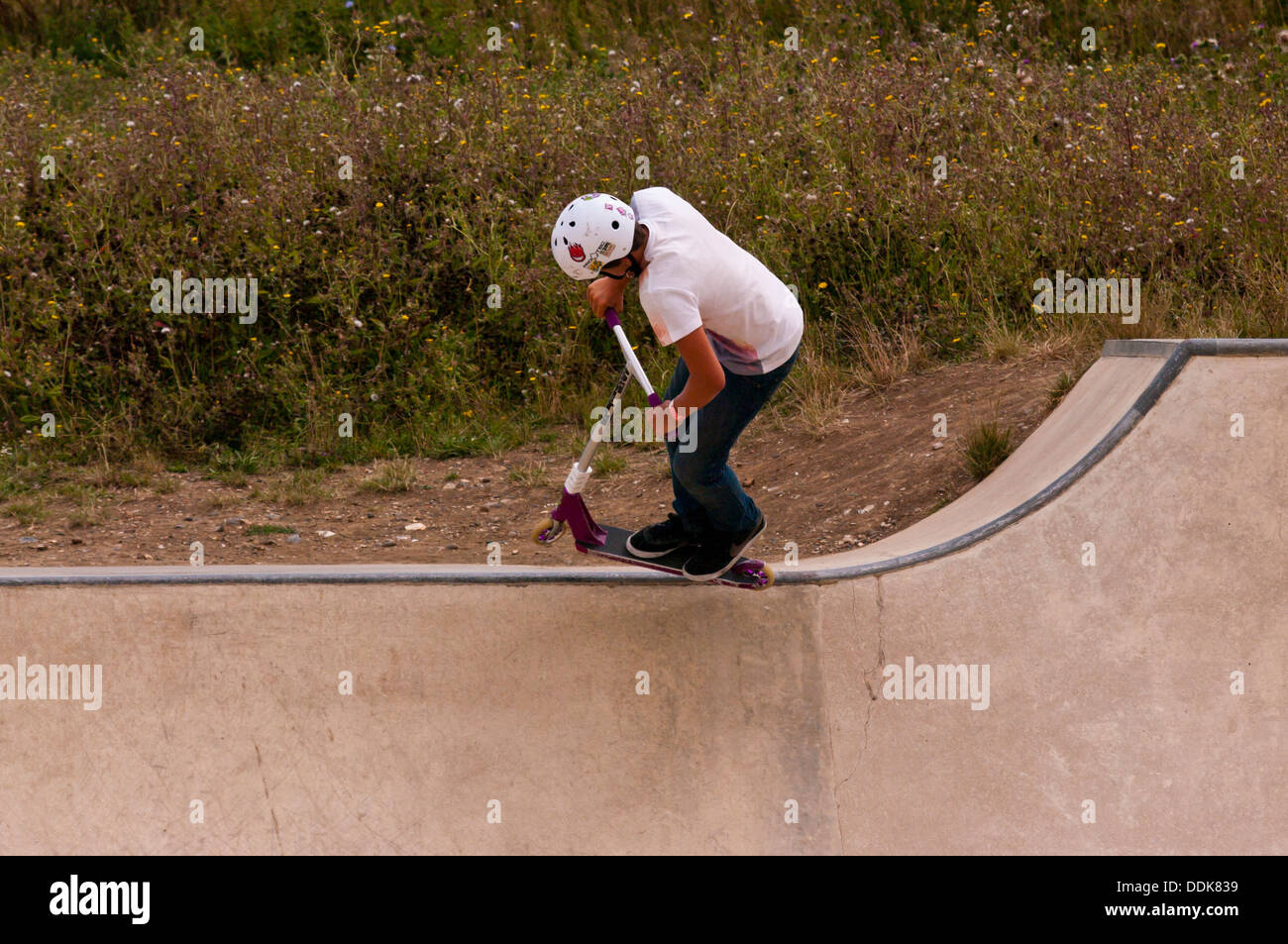Young Boy performing stunts on a scooter - Stock Image