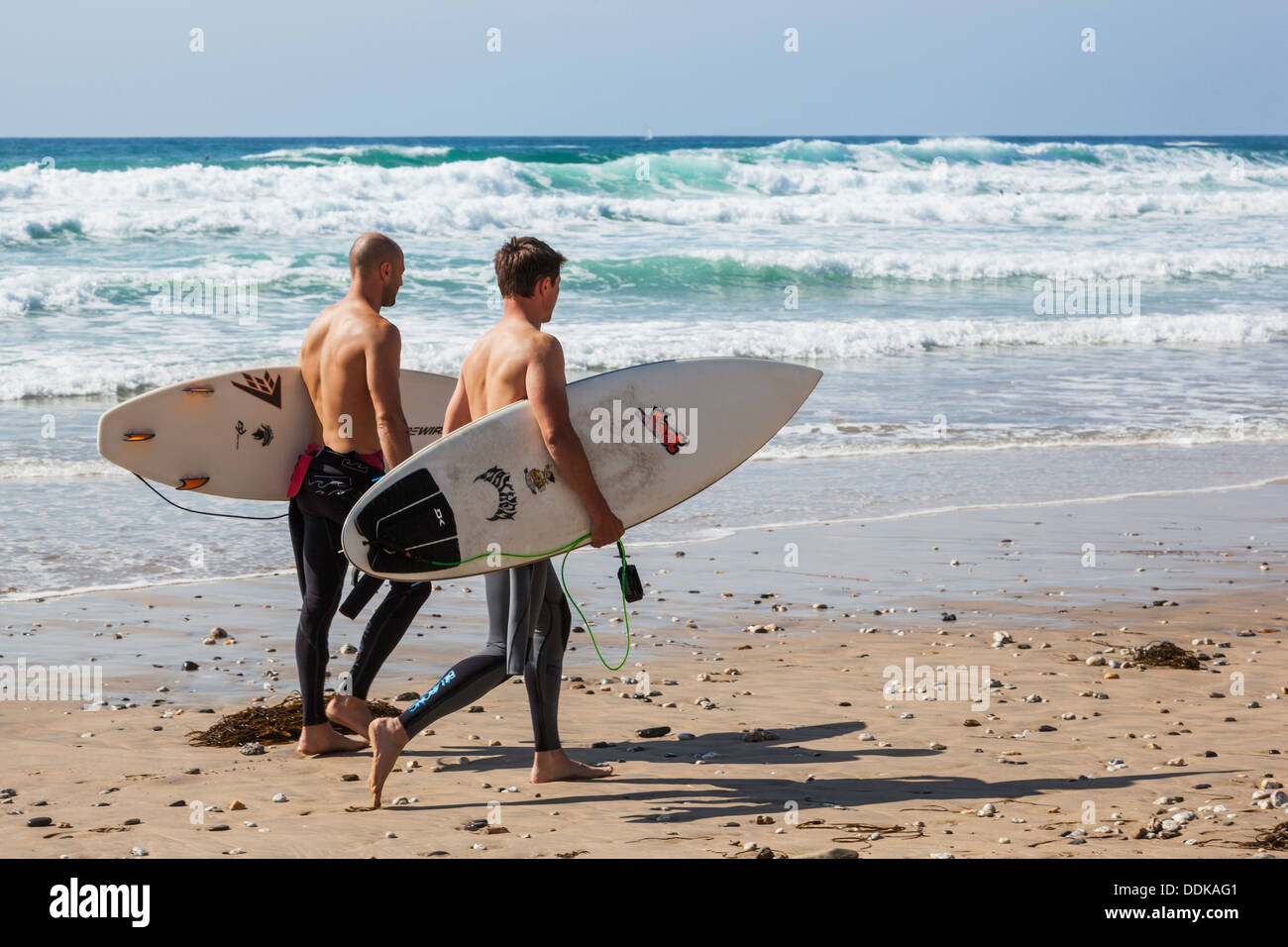 England, Cornwall, Newquay, Fistral Beach, Surfers Walking on Beach - Stock Image