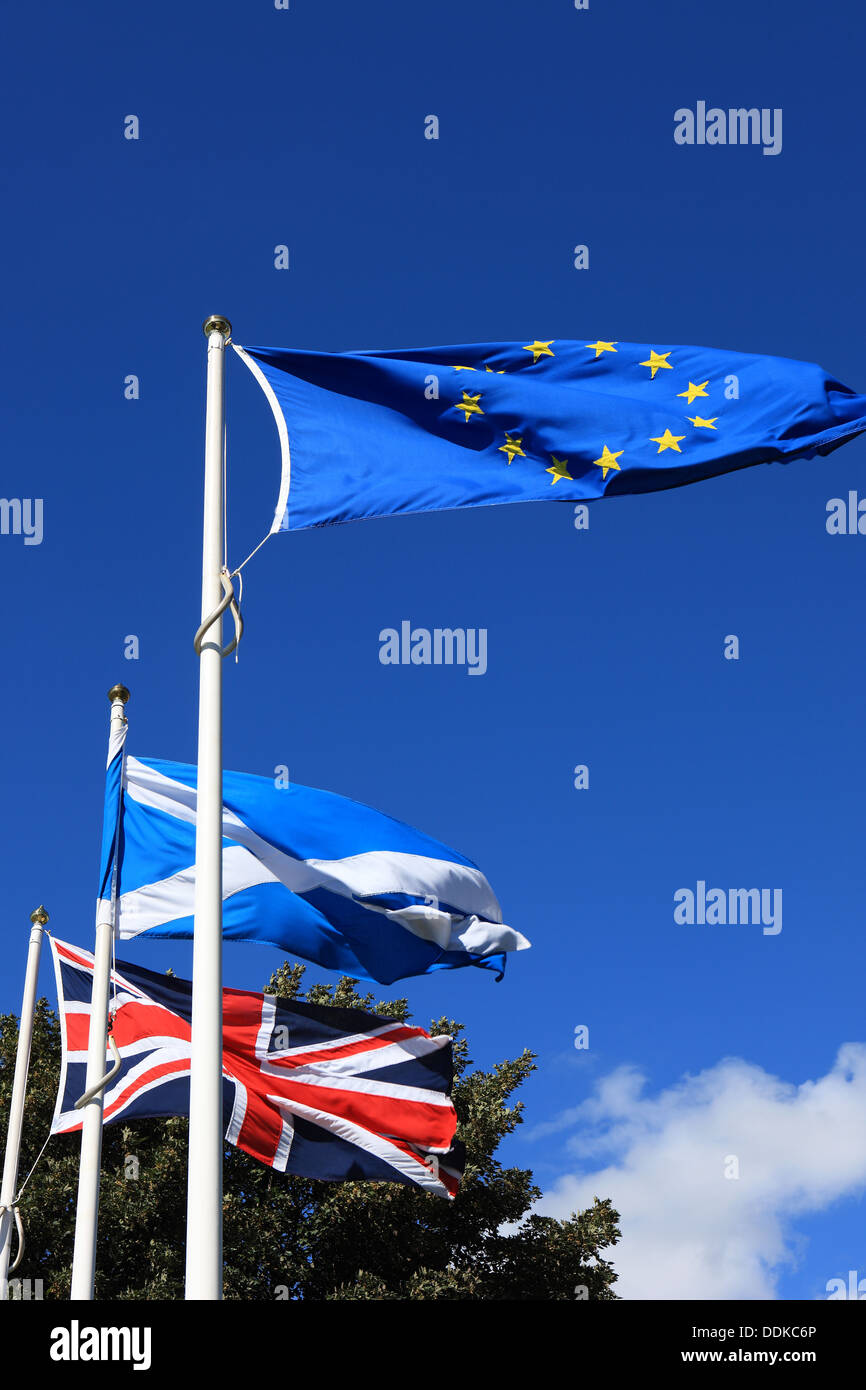 European Union, Scottish and Union Jack flags flying against a blue sky - Stock Image