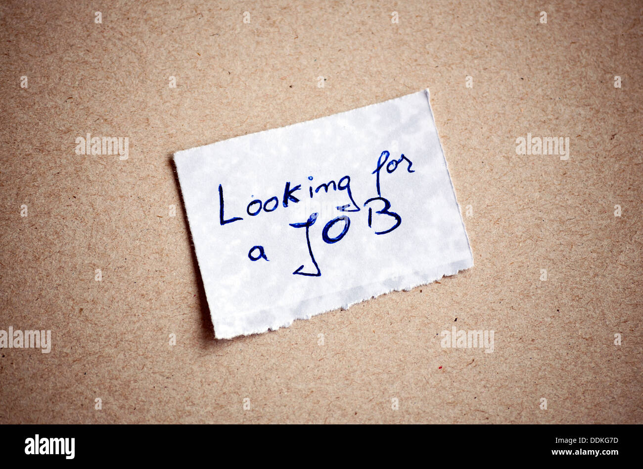 Looking for a Job message,written on piece of paper, on cardboard background. Space for your text. Stock Photo