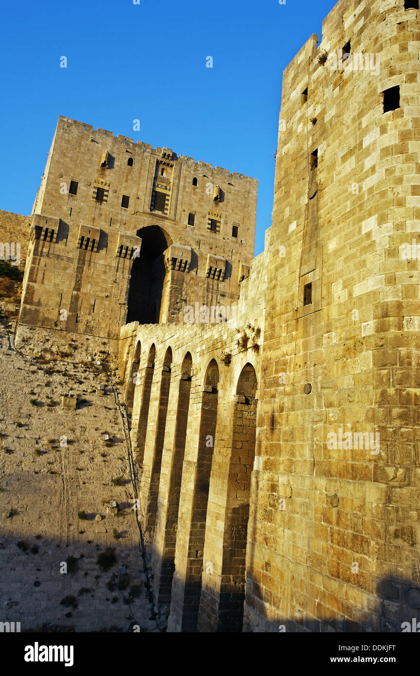 Great Citadel of Aleppo with the glacis defensive mound in the foreground and the monumental gateway and entrance, Syria - Stock Image