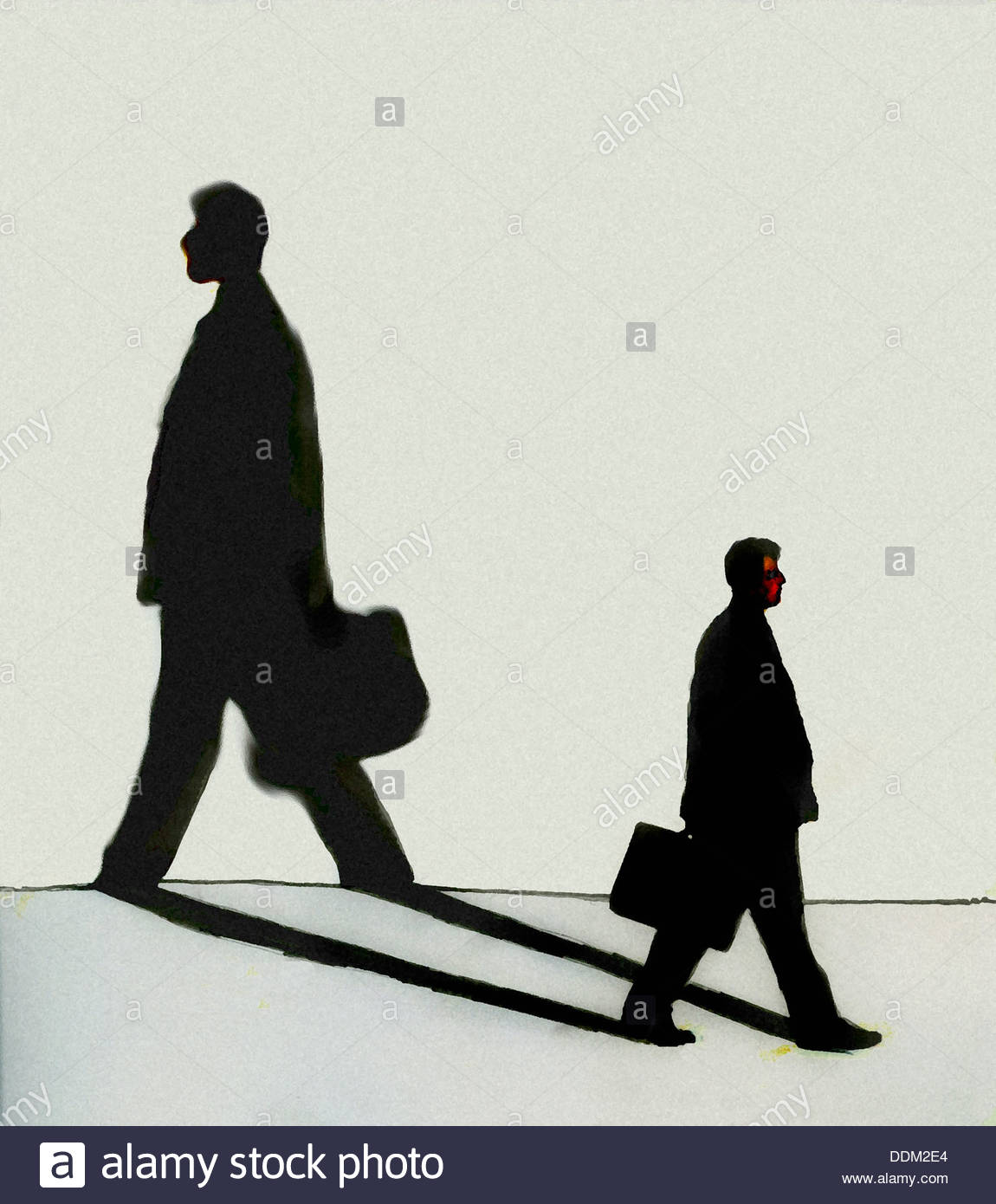 Businessman walking in opposite direction of own shadow - Stock Image
