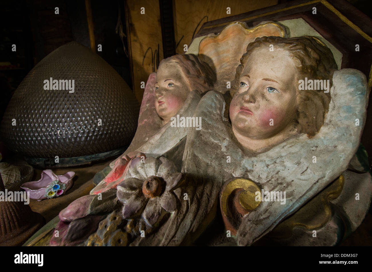Dirty and sooty cherub statuary lies on a shelf amongst other bric-a-brac. - Stock Image