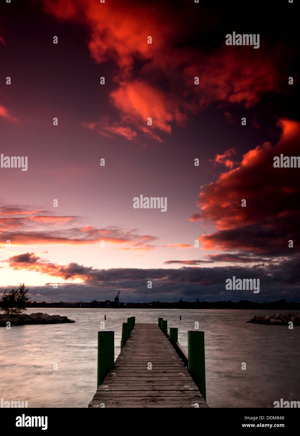 The sun setting over a dock along the Detroit River in Windsor, Ontario. - Stock Image
