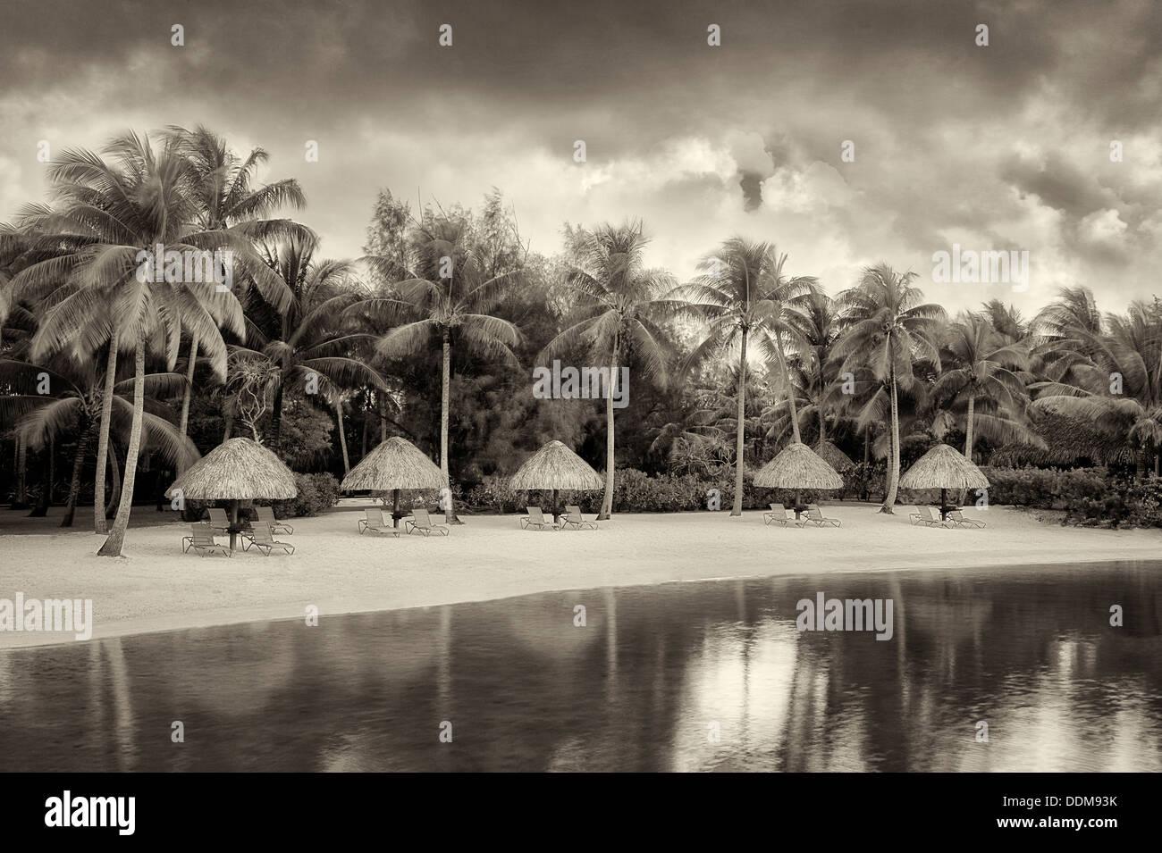 Unbrellas and chairs on lagoon beach. Bora Bora. French Polynesia. - Stock Image