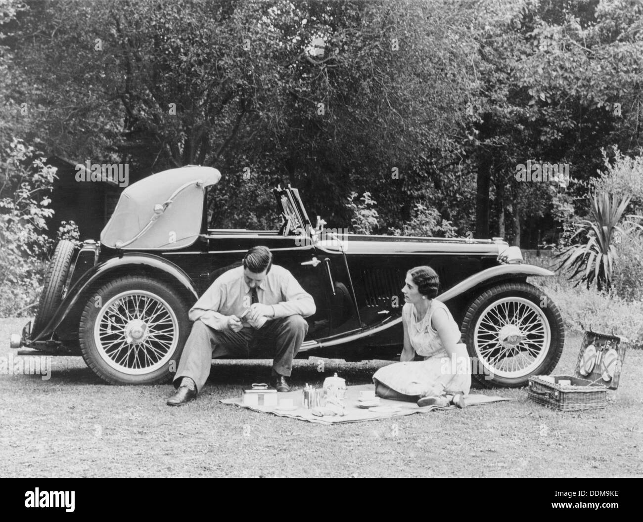 Couple having a picnic by an MG TA Midget, late 1930s. - Stock Image