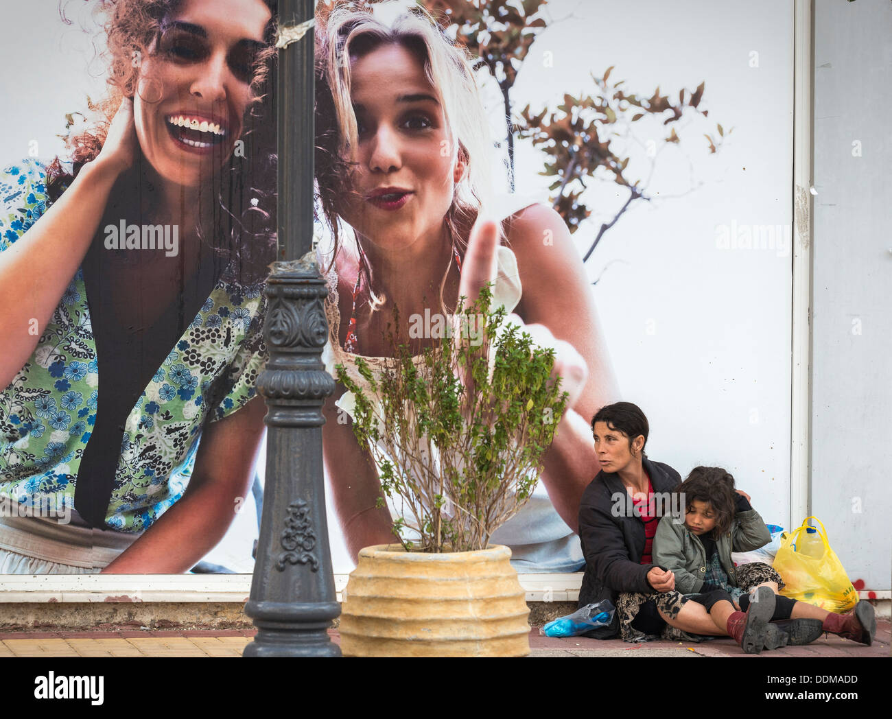 Roma woman and child begging next to a advertising hoarding in the provincial town of Zacharo, Peloponnese, Greece - Stock Image