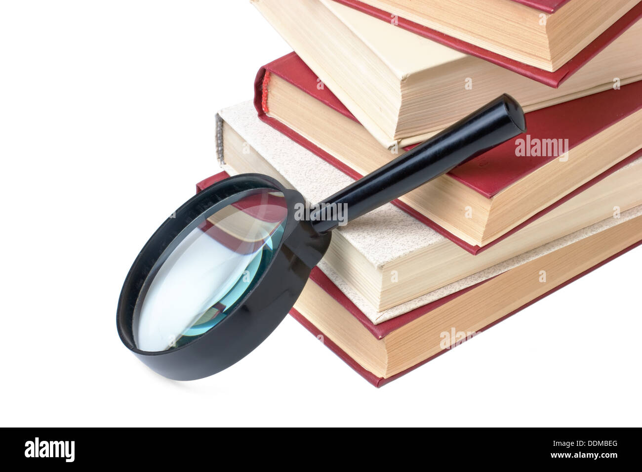 stack of books and magnifying glass isolated - Stock Image