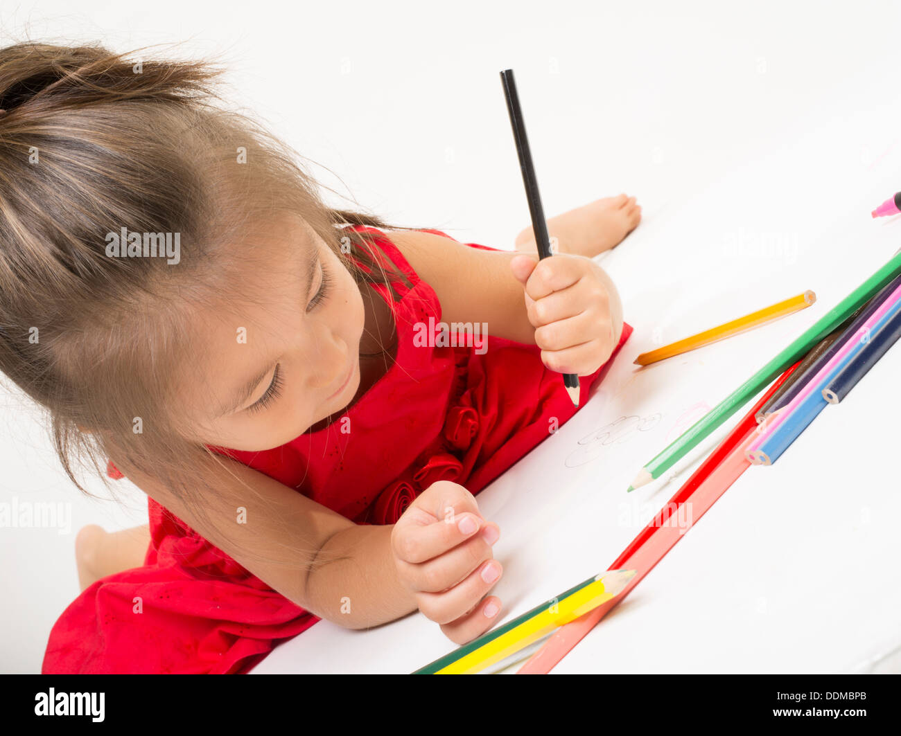 Young girl coloring with colored pencils - Stock Image