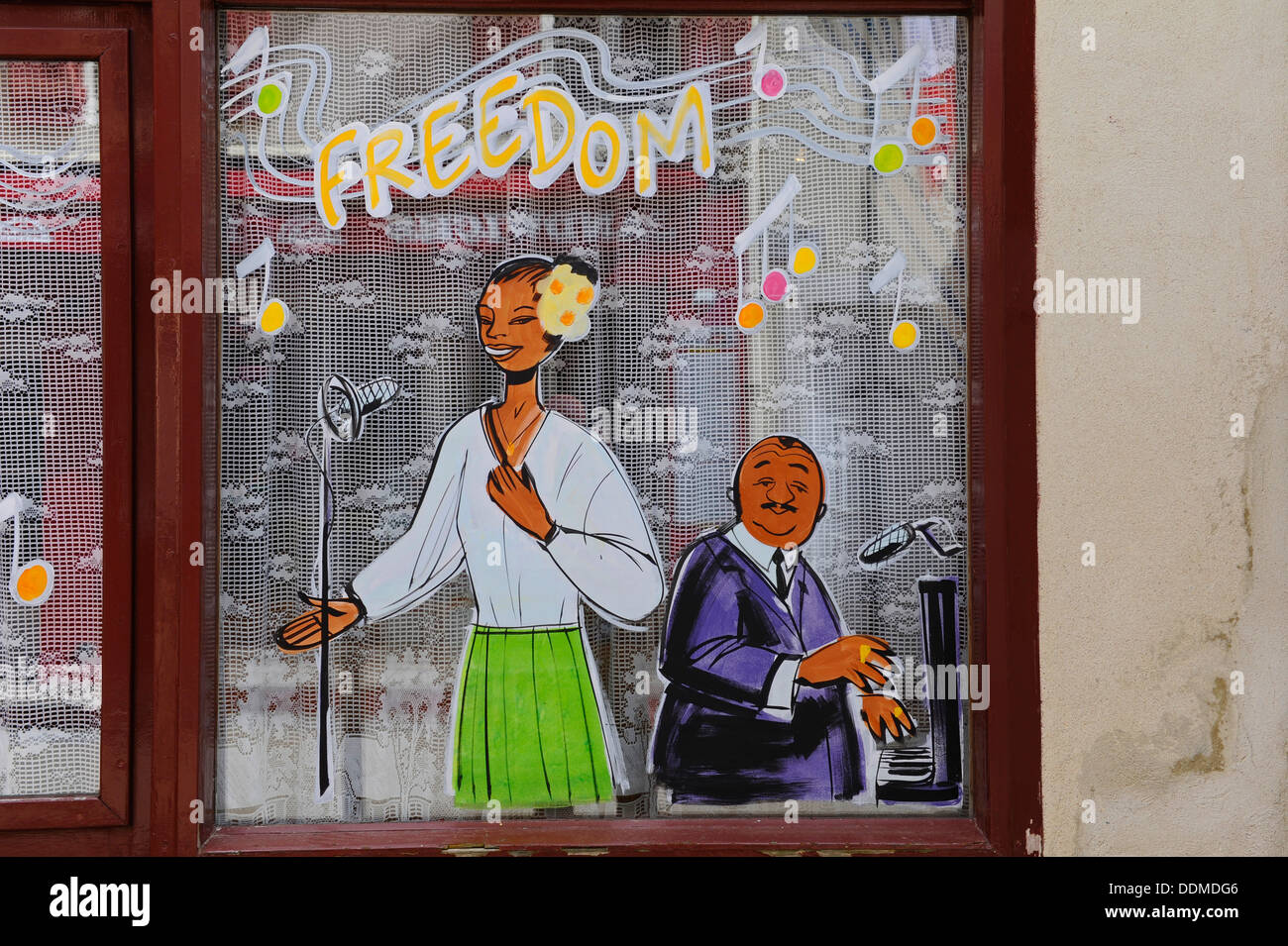 Painting onto a glass window of a female singer and male piano player with freedom being the message. - Stock Image