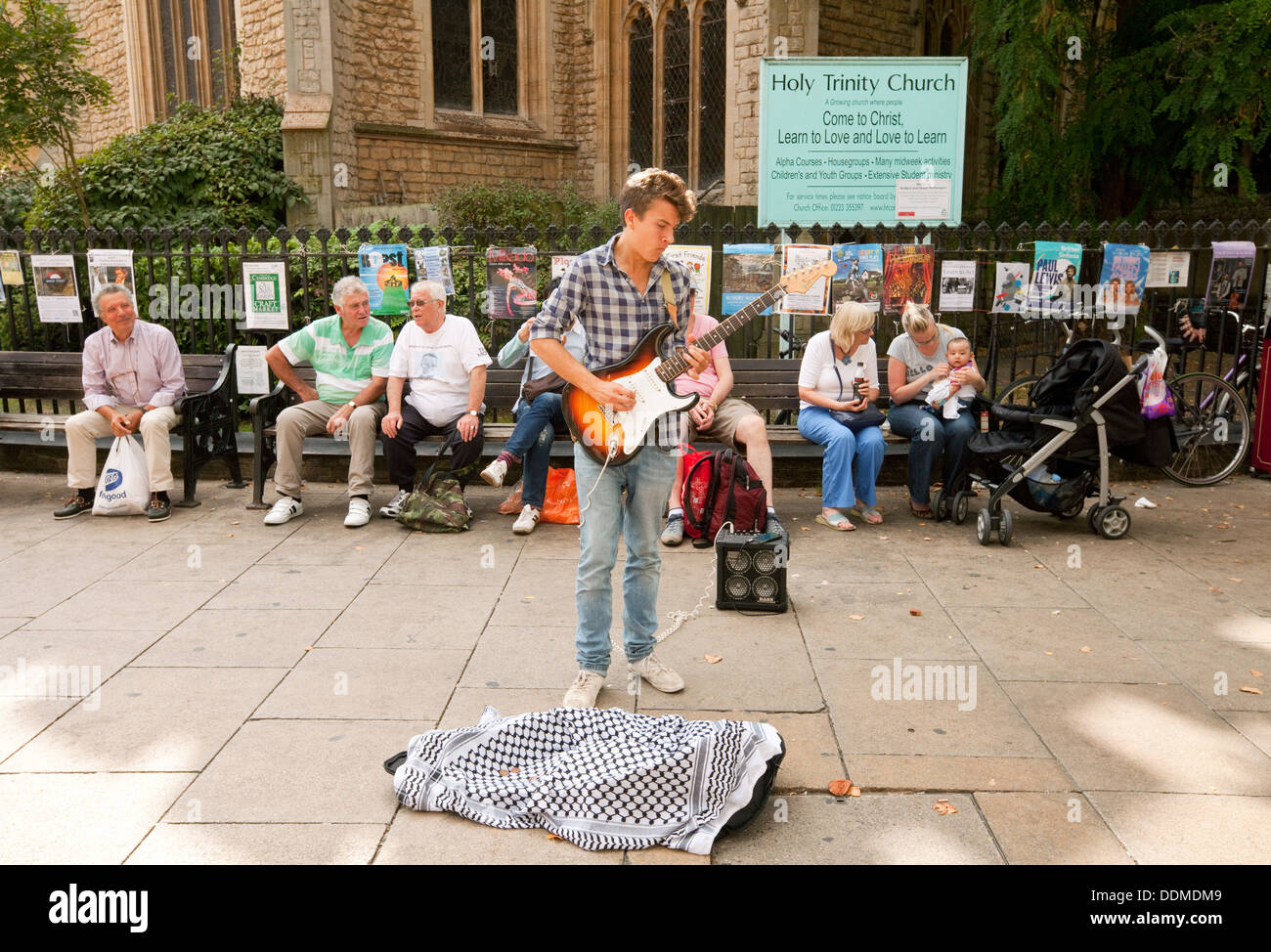 A street musician or busker, playing a guitar, St Andrews St, Cambridge city centre UK - Stock Image
