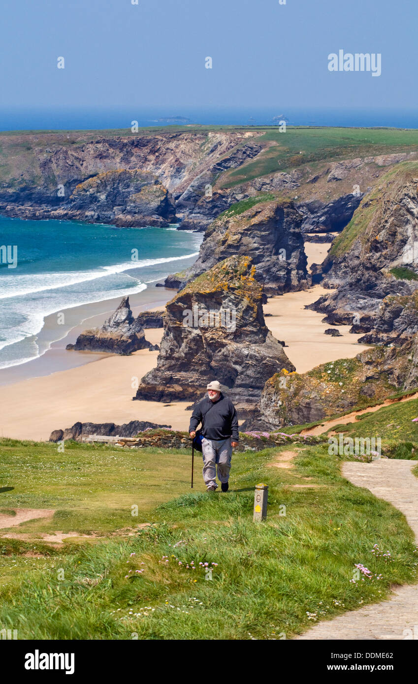 Hiker walking on the South West Coast Path near Bedruthan Steps on the coast of north Cornwall, England, UK - Stock Image