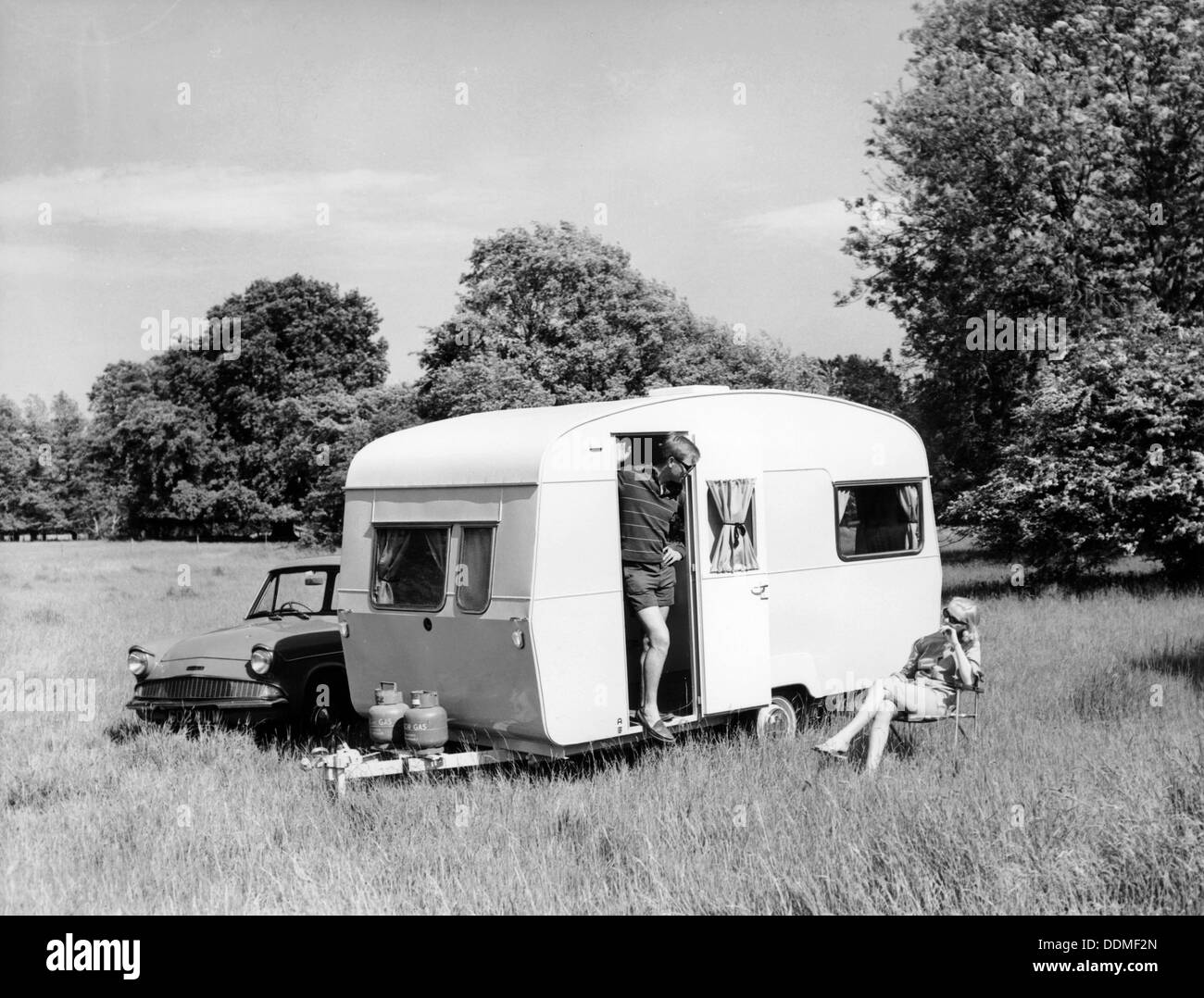 Couple on holiday with their 1963 Sprite Alpine caravan, (c1963?). - Stock Image