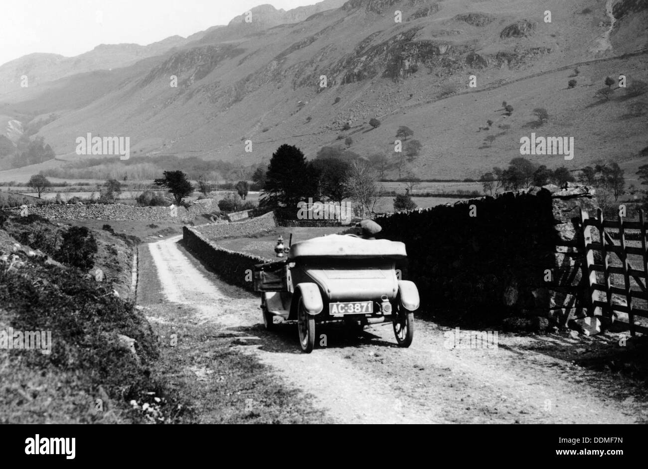 A vintage car travelling along a lane through the Lake District, Cumbria, 1920s. - Stock Image