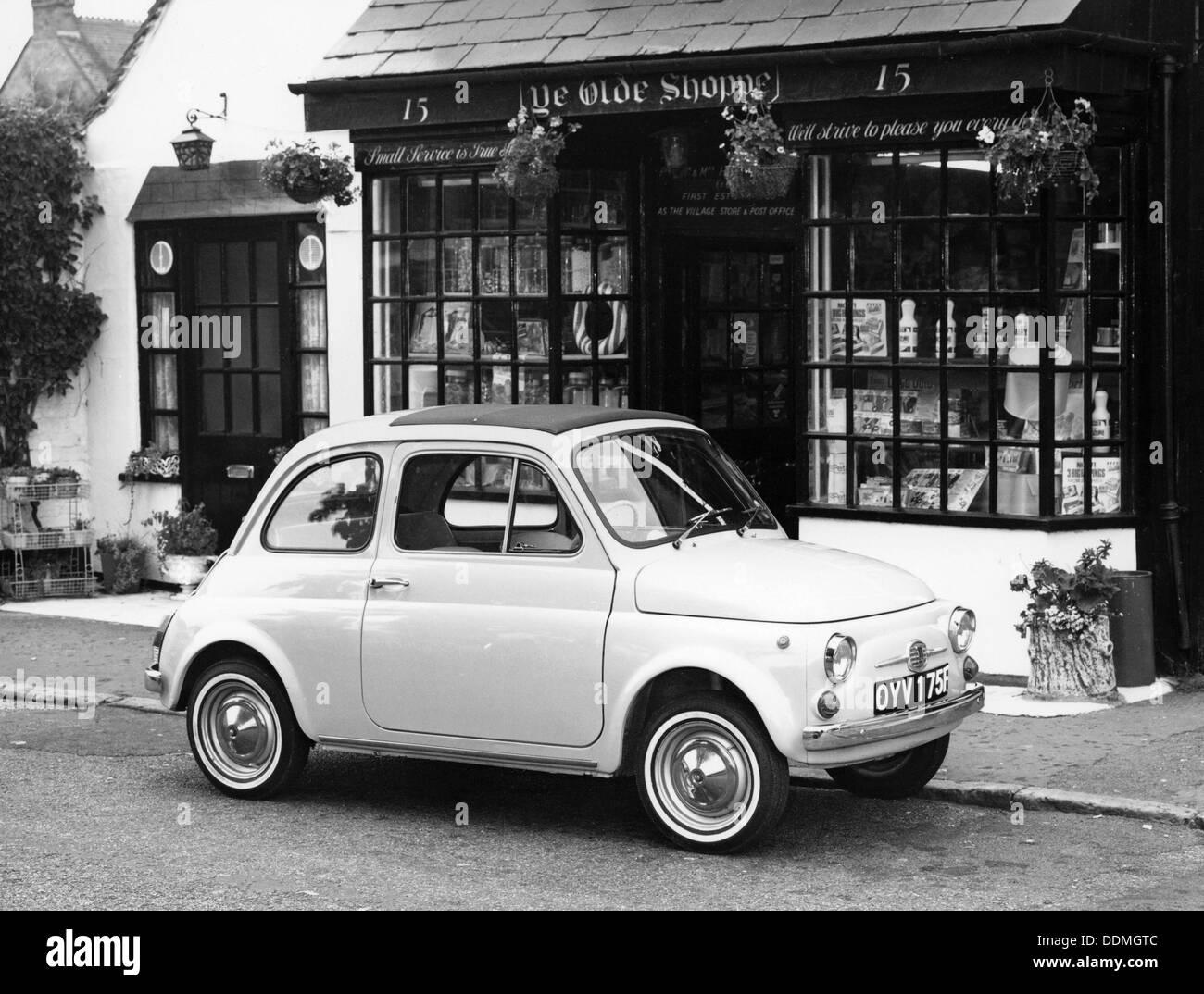 Fiat 500 parked outside a quaint shop, 1969. - Stock Image