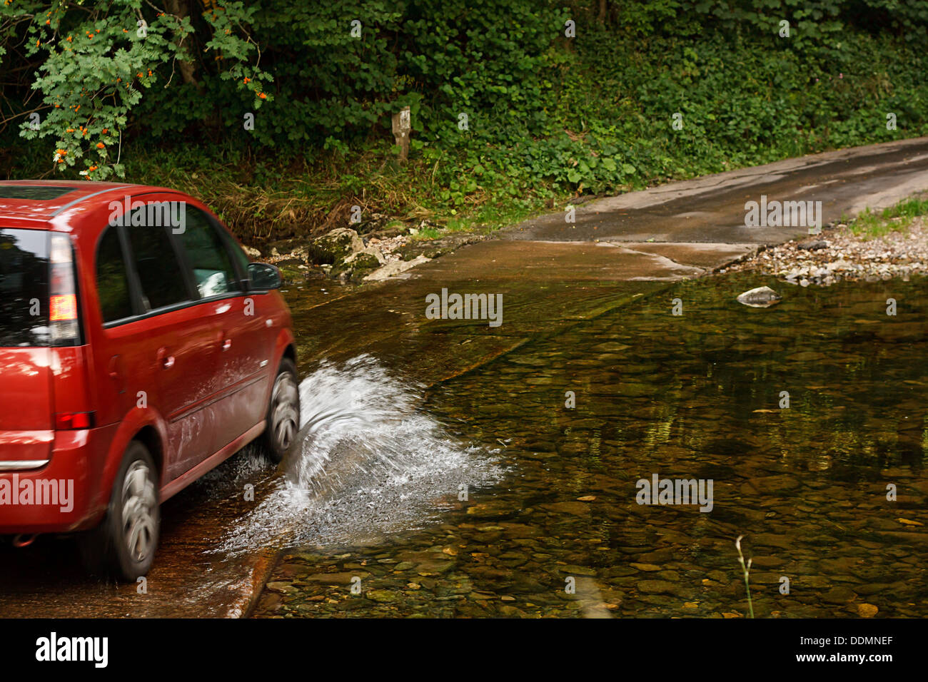 Family Car fording a river at ford an old fashioned way of crossing water without building a bridge - Stock Image