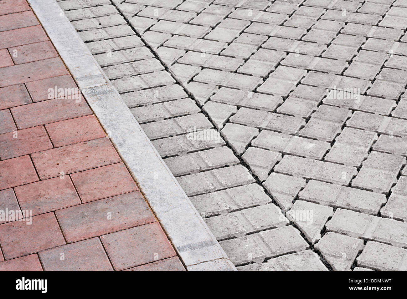Brick paving types with pink sidewalk, curb and drive made from plain interlocking concrete bricks - Stock Image