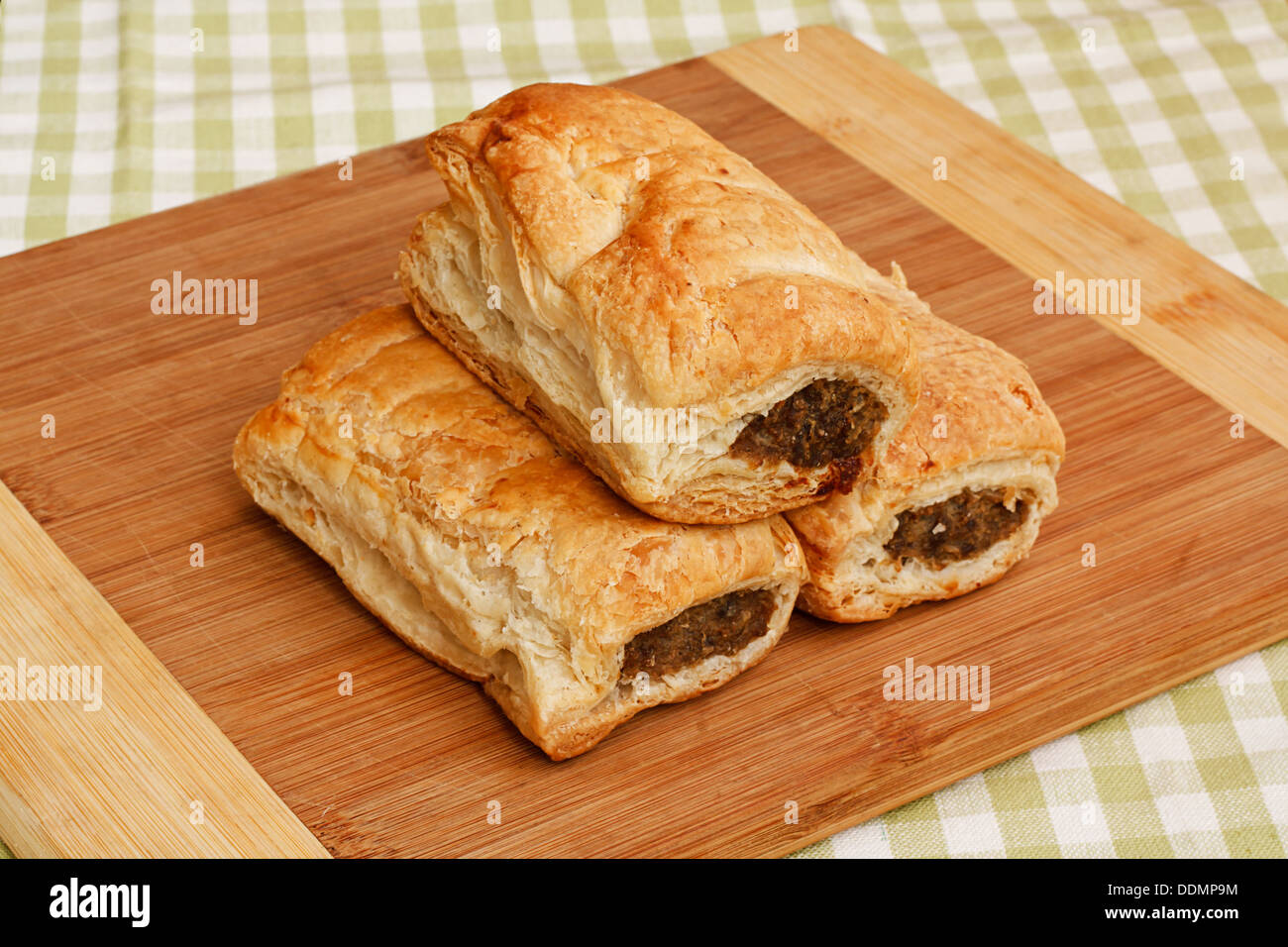 Three traditional sausage rolls on a rustic cafe table setting, a popular pastry snack available from british bakers - Stock Image