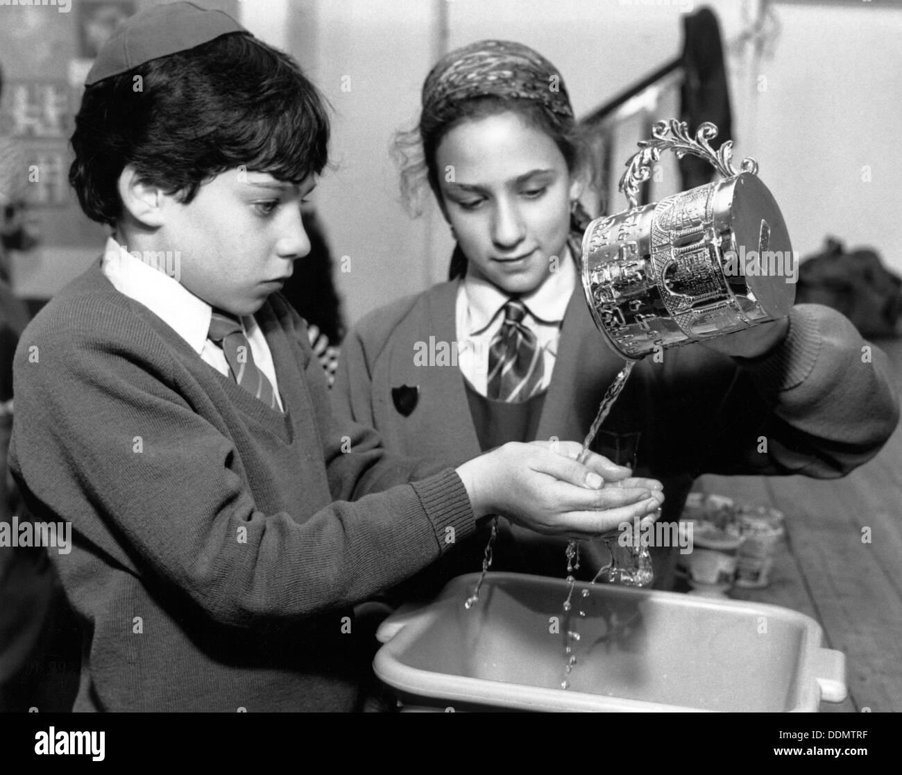 Jewish children performing ritual hand-washing, April 1991. Artist: Sidney Harris - Stock Image