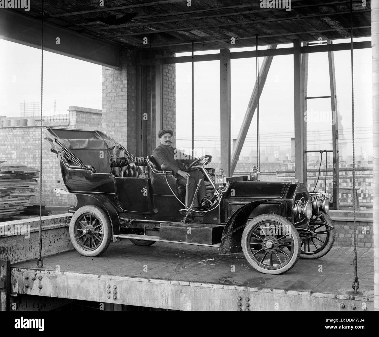 A car and chauffeur in the car lift at Mitchell's Motors, Wardour Street, London, 1907. Artist: Bedford Lemere and Company - Stock Image