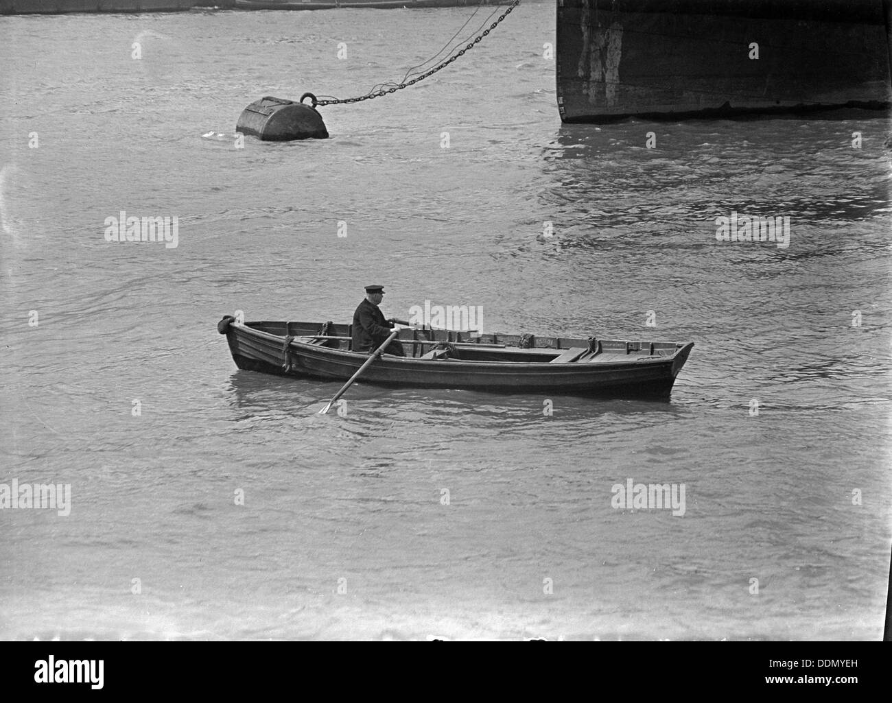 A man rowing a boat in London docks, c1945-c1965. Artist: SW Rawlings - Stock Image