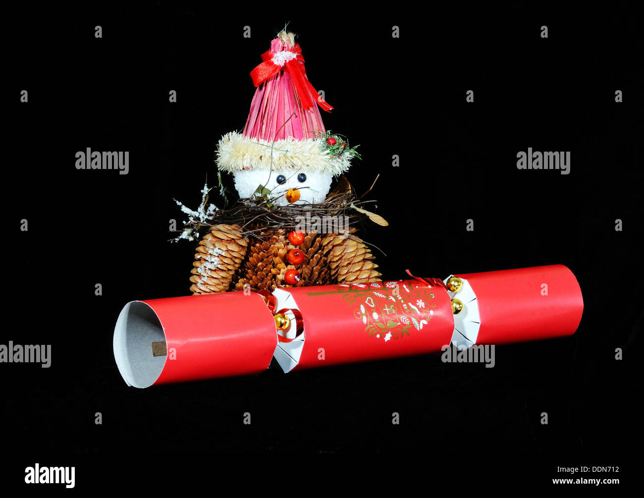 Christmas cracker hats stock photos christmas cracker hats stock snowman made from pinecones with a red christmas cracker set against a black background solutioingenieria Images