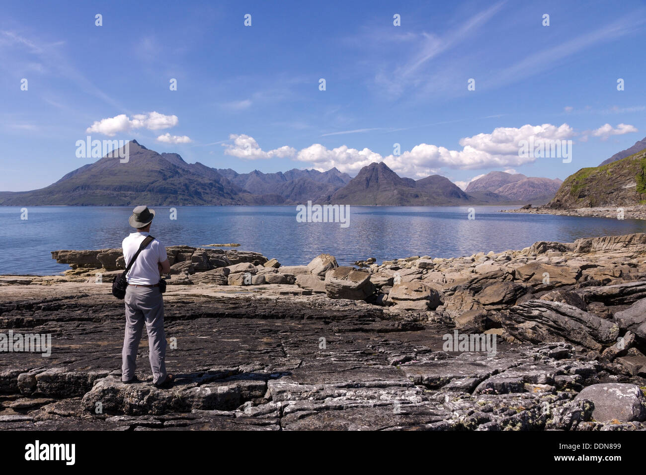 Male holidaymaker admiring view from Elgol over Sea Loch Scavaig to the Black Cuillin mountains, Isle of Skye, Scotland, UK - Stock Image