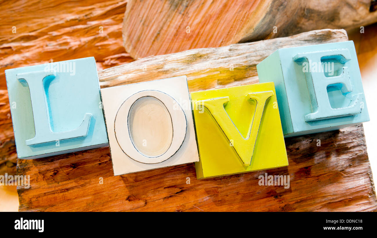 The word Love spelled out in big block letters on a rustic wooden background Stock Photo