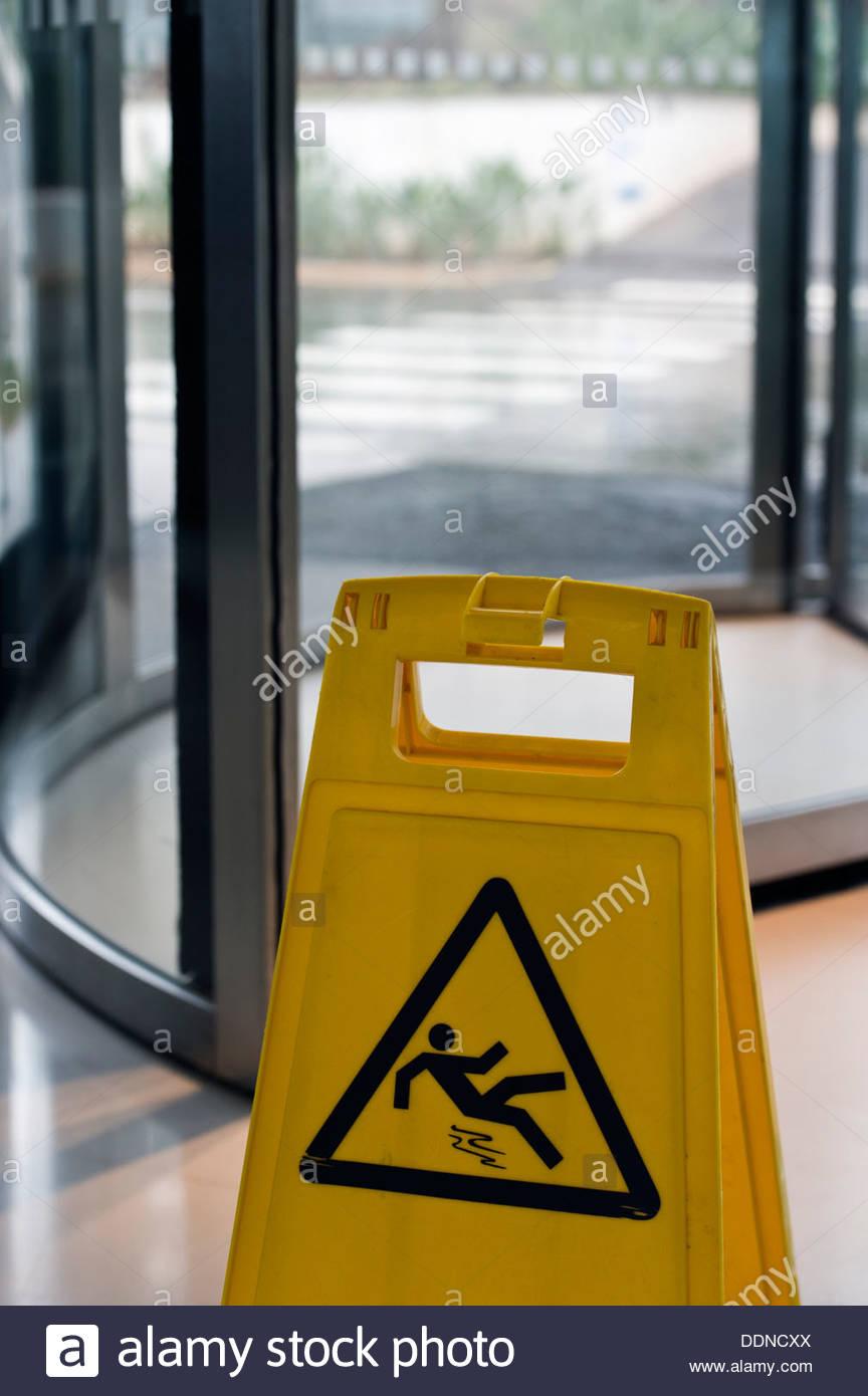 Warning sign slippery when wet in front of revolving door - Stock Image