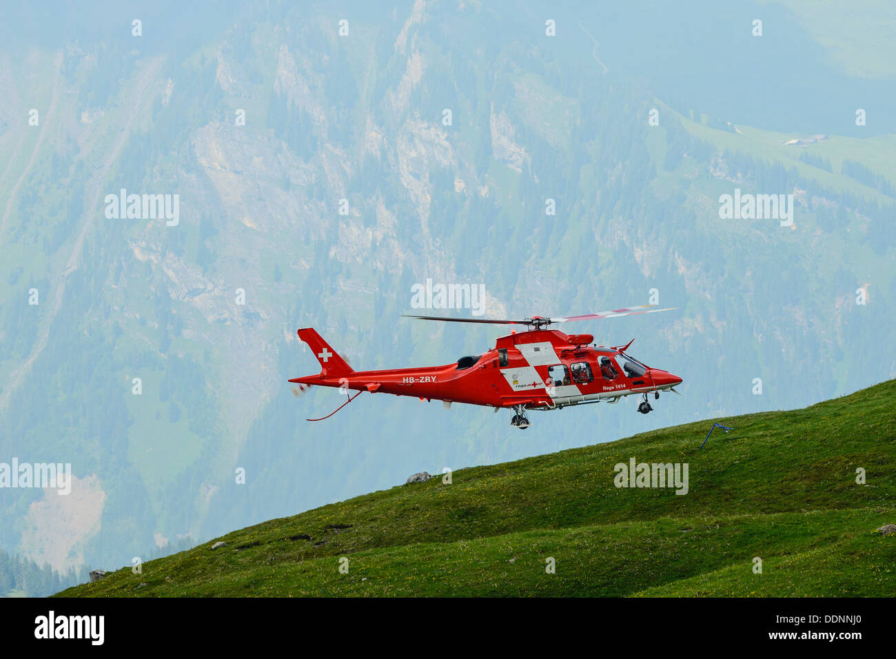 AgustaWestland Da Vinci helicopter of the Swiss Air rescue service REGA in action near Grindelwald - Stock Image