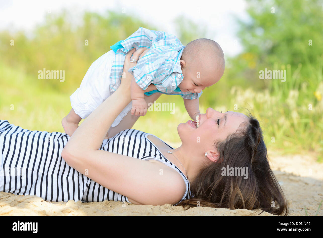 Happy mother holding baby outdoors - Stock Image