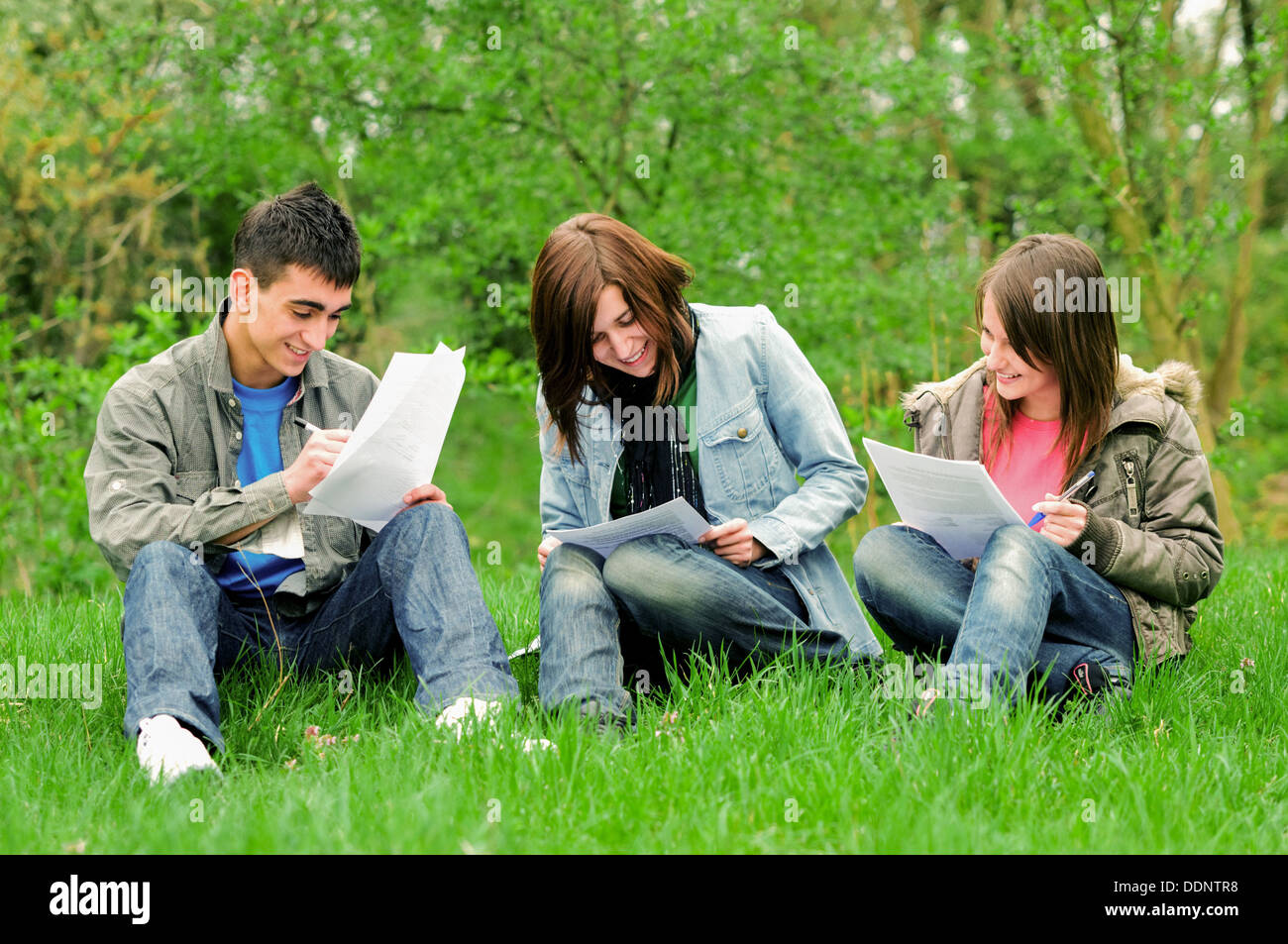 Three high school students learning together outdoor - Stock Image