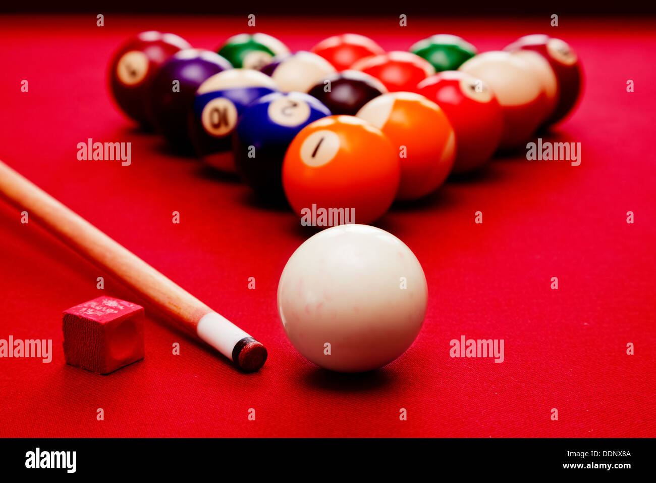 Billiards pool game. Cue ball, cue, color balls in triangle, chalk. Red cloth table - Stock Image