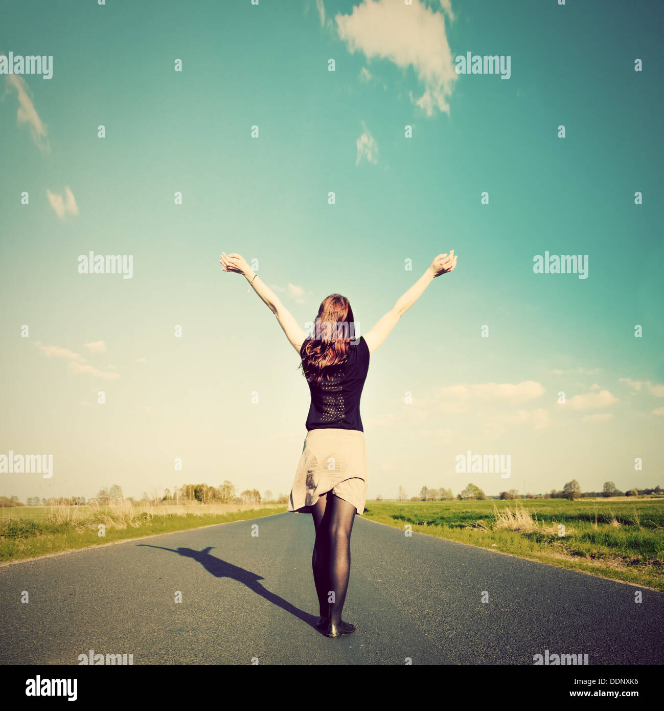 Happy woman standing with hands up on straight road facing sun. Future / freedom / hope / success concept - Stock Image