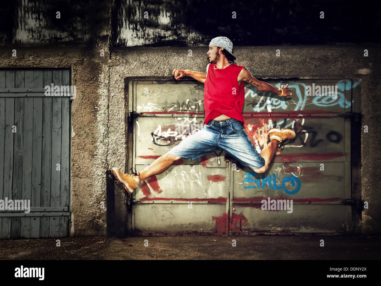 Young man / teen jumping / dancing on grunge graffiti wall background - Stock Image