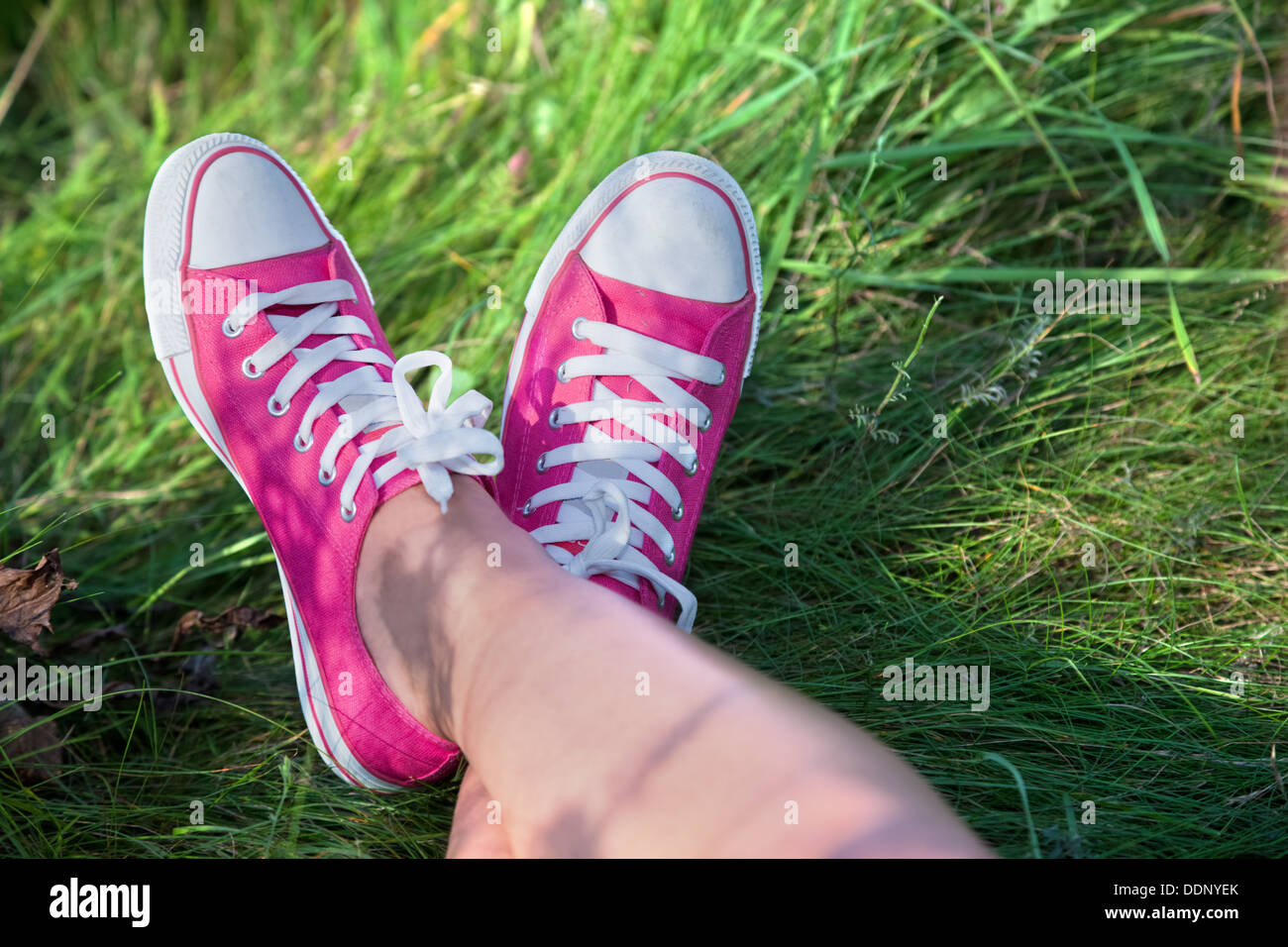 Woman wearing pink trainers with legs crossed outside - point of view - Stock Image