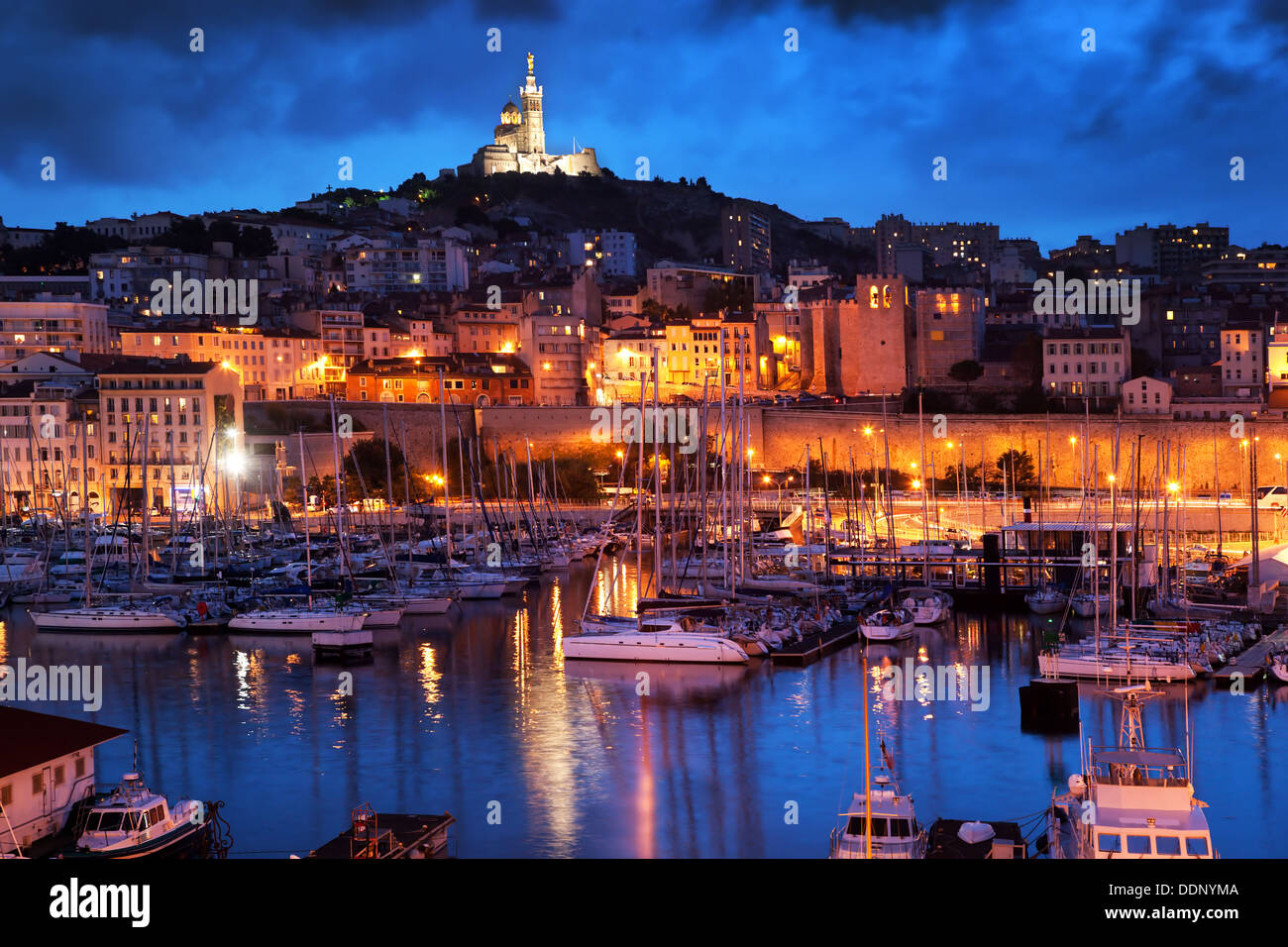 Marseille, Old Port harbour / Vieux Port, France at night with view of the Notre Dame de la Garde on the hill at night - Stock Image