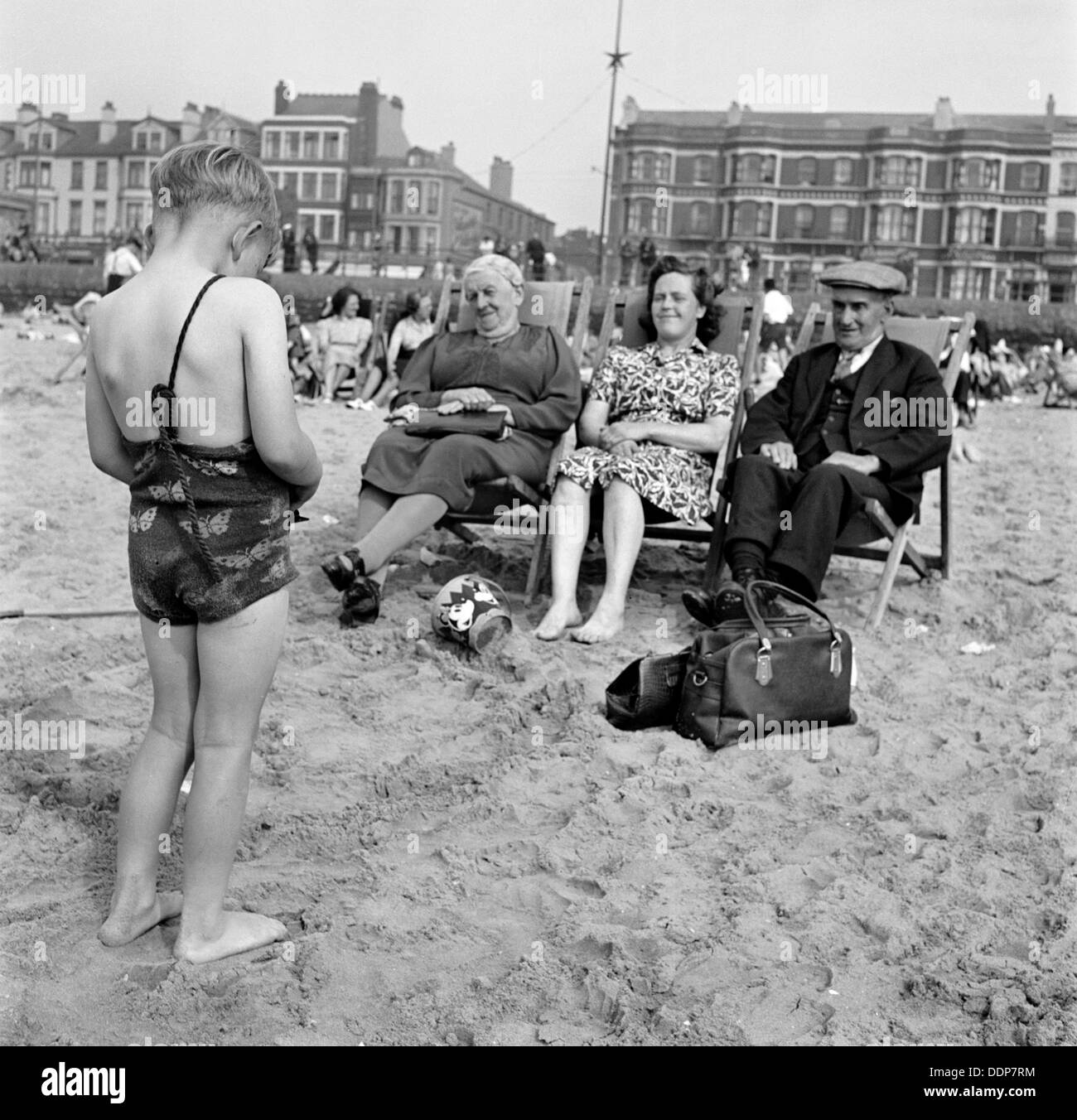 A child photographs his mother and grandparents on the beach, Blackpool, c1946-c1955. Artist: John Gay - Stock Image