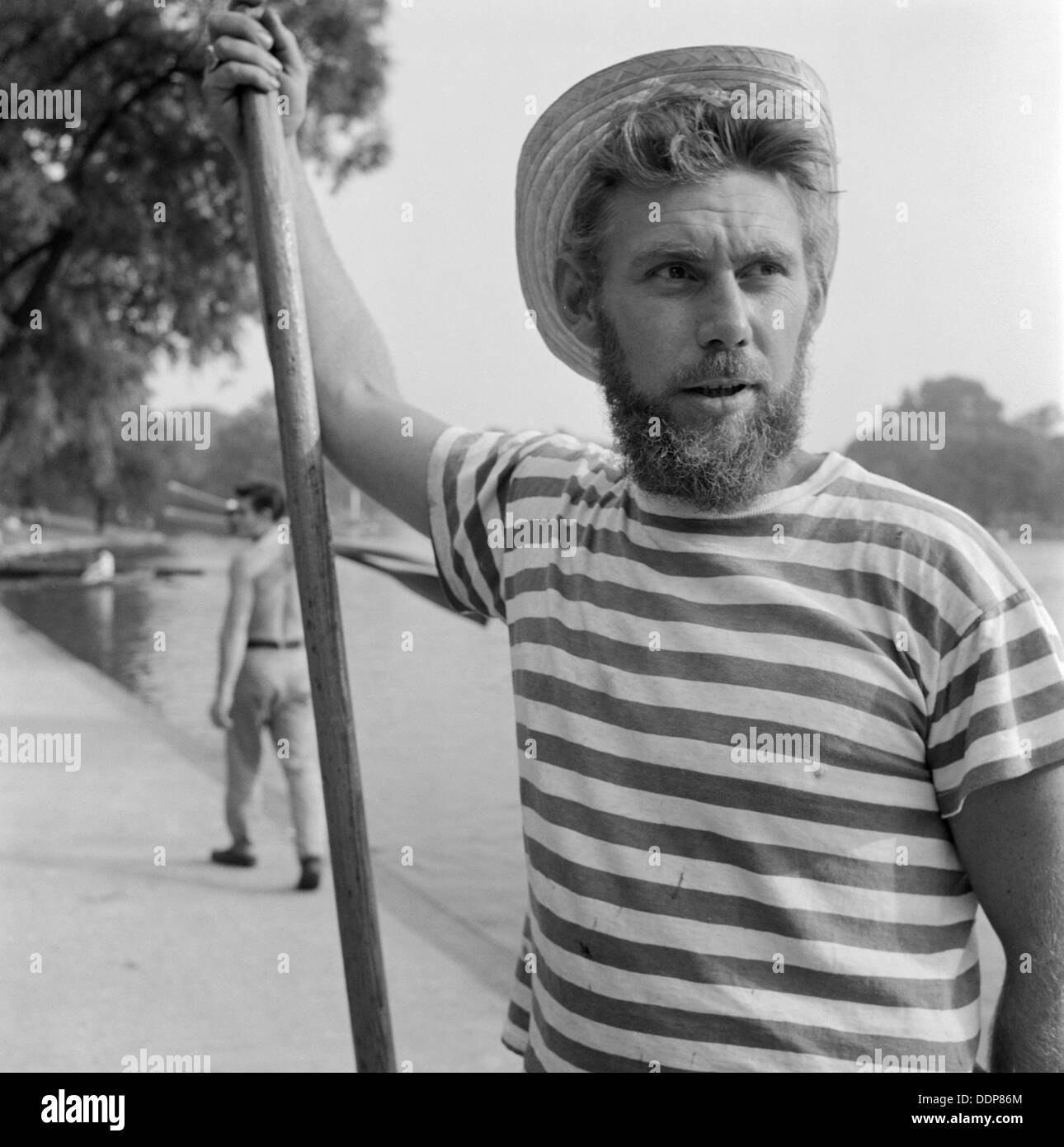An boatman wearing a stripey T-shirt and a straw boater, Greater London, c1946-c1959. Artist: John Gay - Stock Image